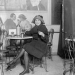 Woman at a soda fountain pouring alcohol out of a compartment in her cane, 1922