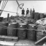"Prohibition agents examining barrels on board a ""rum runner"" boat after it had been chased and captured by the Coast Guard cutter USS Seneca, 1924"