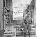An SA soldier in Berlin standing in front of a sign urging the general public not to shop at stores with Jewish owners, spring 1933