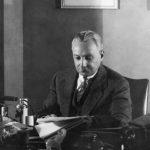 Florenz Ziegfeld reads behind a desk, 1930