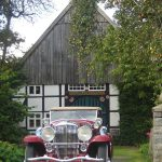 A Duesenberg J Murphy Convertible Coupe in front of Fred and August Duesenberg's house of birth