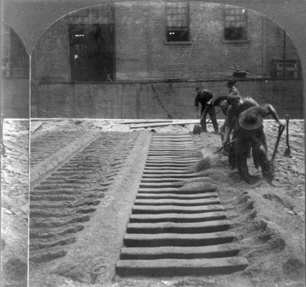 Workers making sand molds to produce pig iron at a blast furnace in Pittsburgh, Pennsylvania. ca. 1905