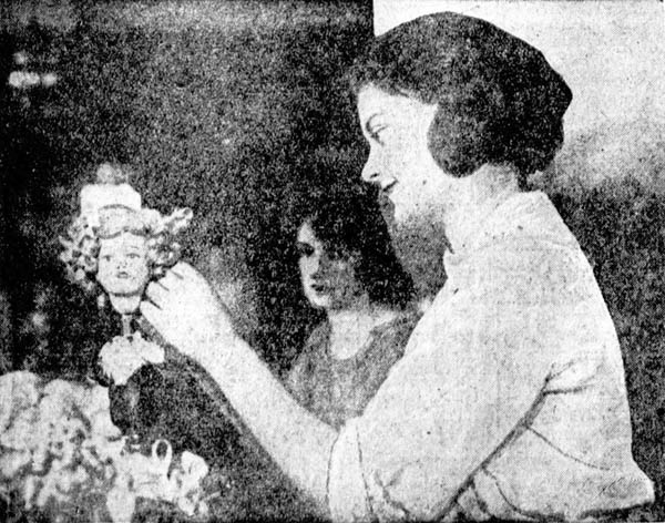 """""""Curling the doll's hair and gets paid for it,"""" 1920"""