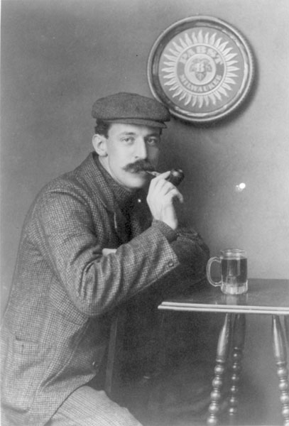 Man drinking a mug of beer under a Pabst - Milwaukee sign around 1900