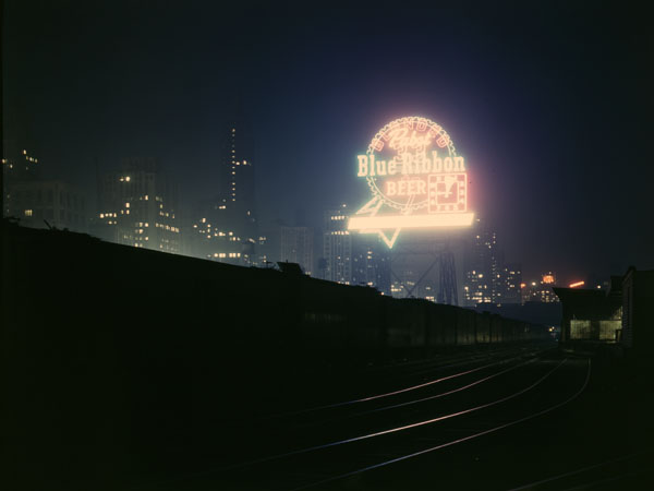 Illinois Central Railroad freight cars in the South Water Street freight terminal, Chicago, Illinois, with a neon Pabst Blue Ribbon sign in the background