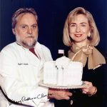 Walter Staib presents Hillary Rodham Clinton with a cake replica of the White House