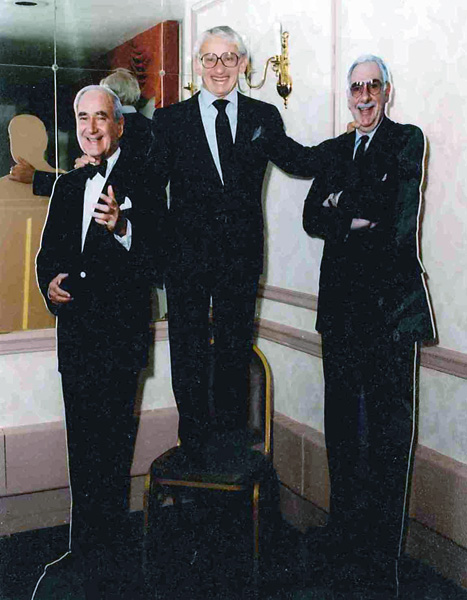 Dan Aaron at his retirement party flanked by full-size cutout photos of Comcast co-founders Ralph Roberts and Julian Brodsky, 1991